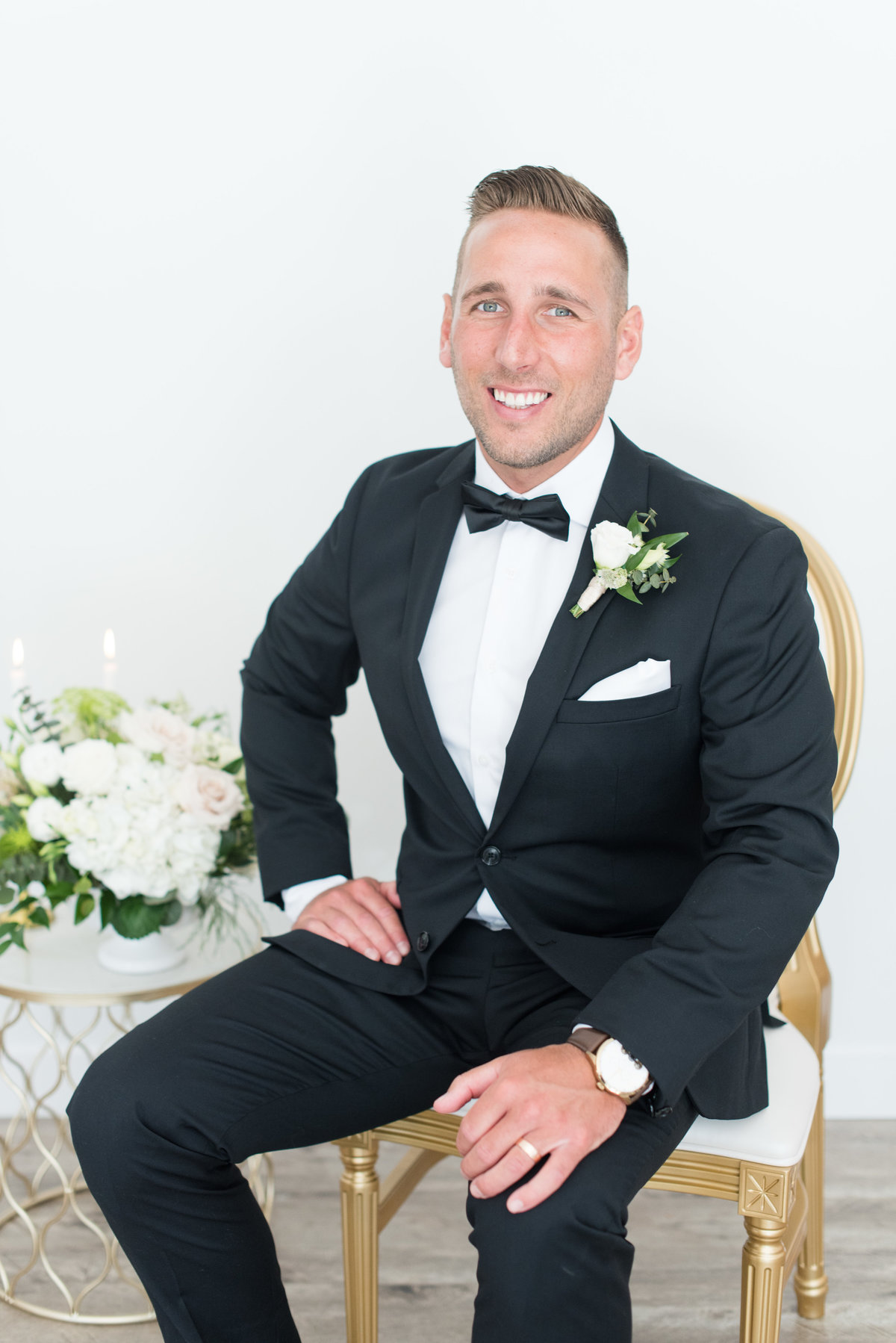 Groom sitting on King Louis chair from Tents & Events in his suit from J.B Evans in Thunder Bay