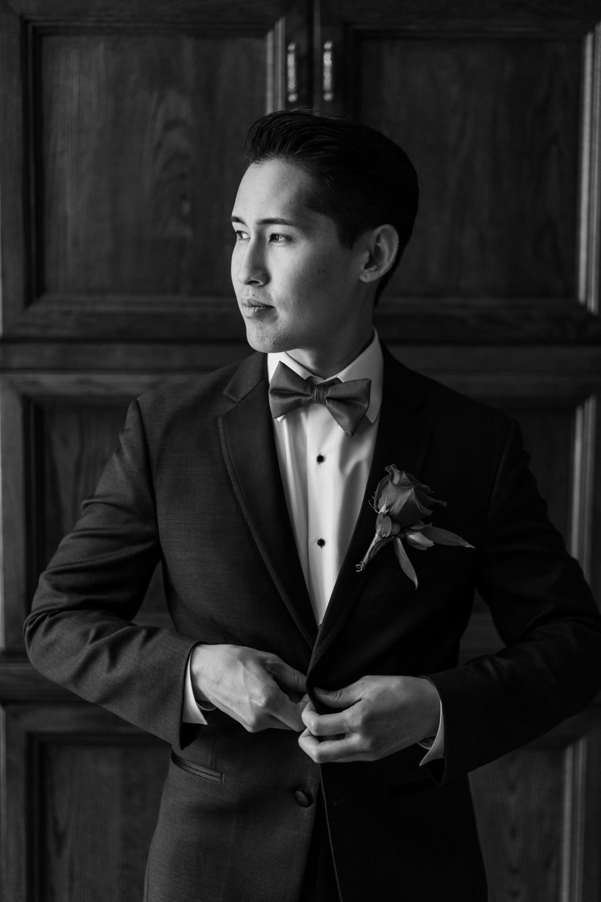 black and white photo of groom buttoning shirt