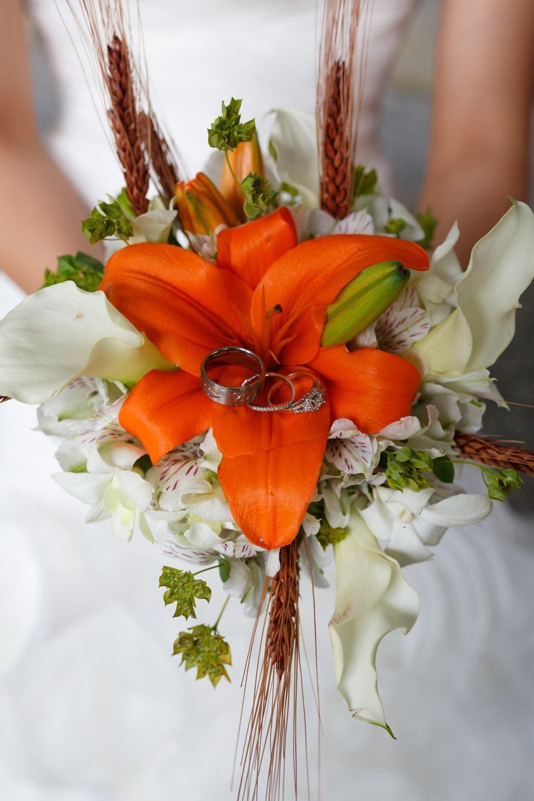 bride holds wedding rings with tiger lily bouquet