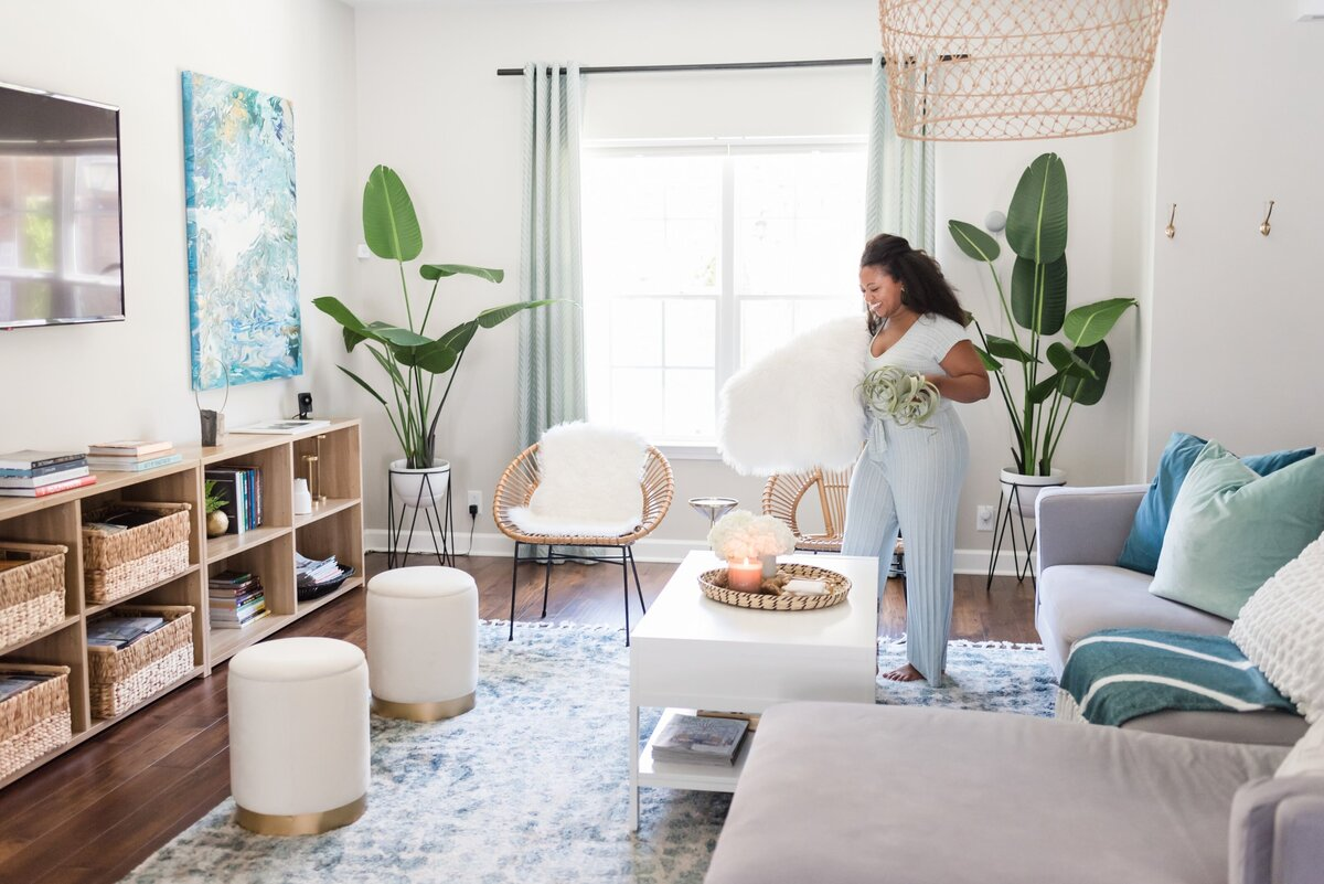 Nashville interior designer walking around her living room with a plant and a pillow in her arms
