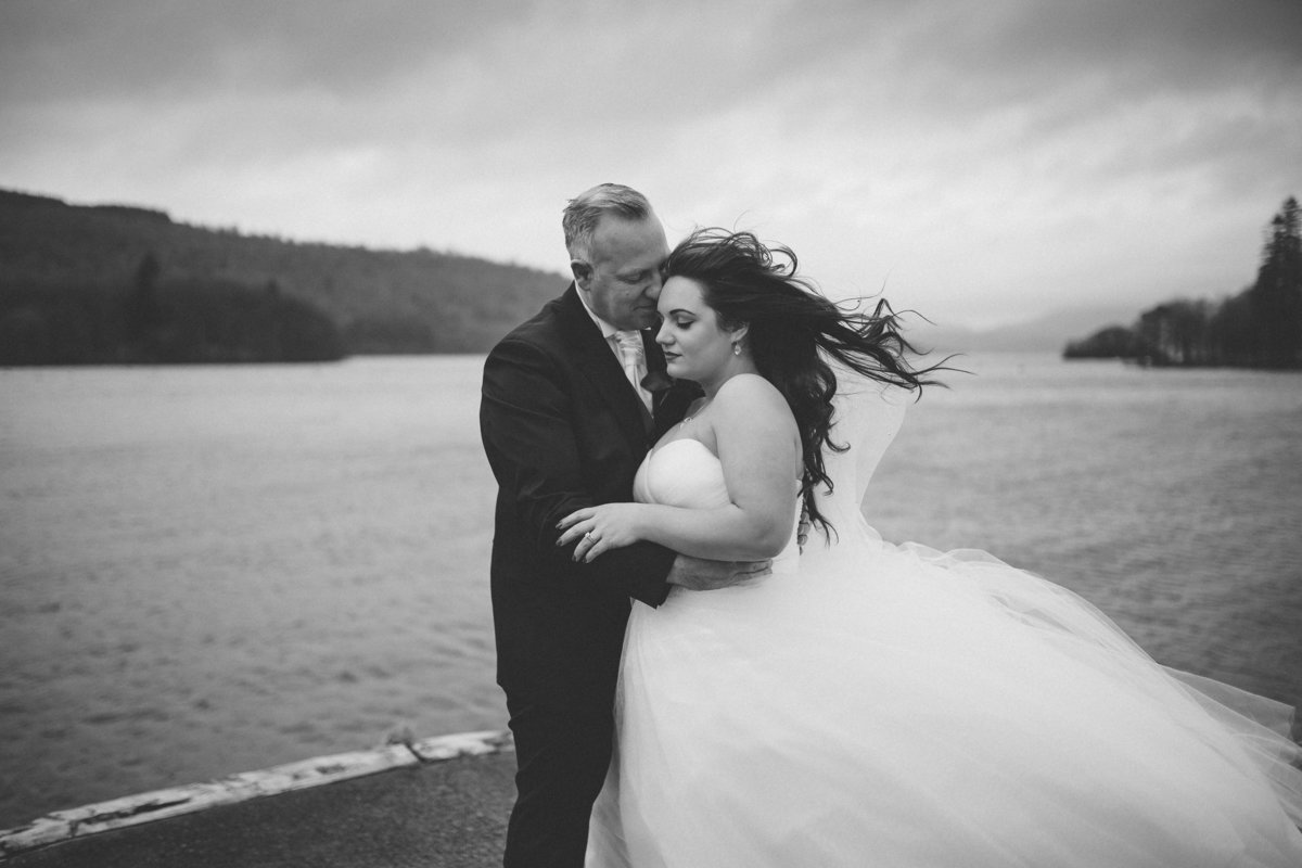 Couple stood on edge of Lake Windermere embracing as Brides hair blows in the wind by Lake District Wedding  Photographer Jono Symonds