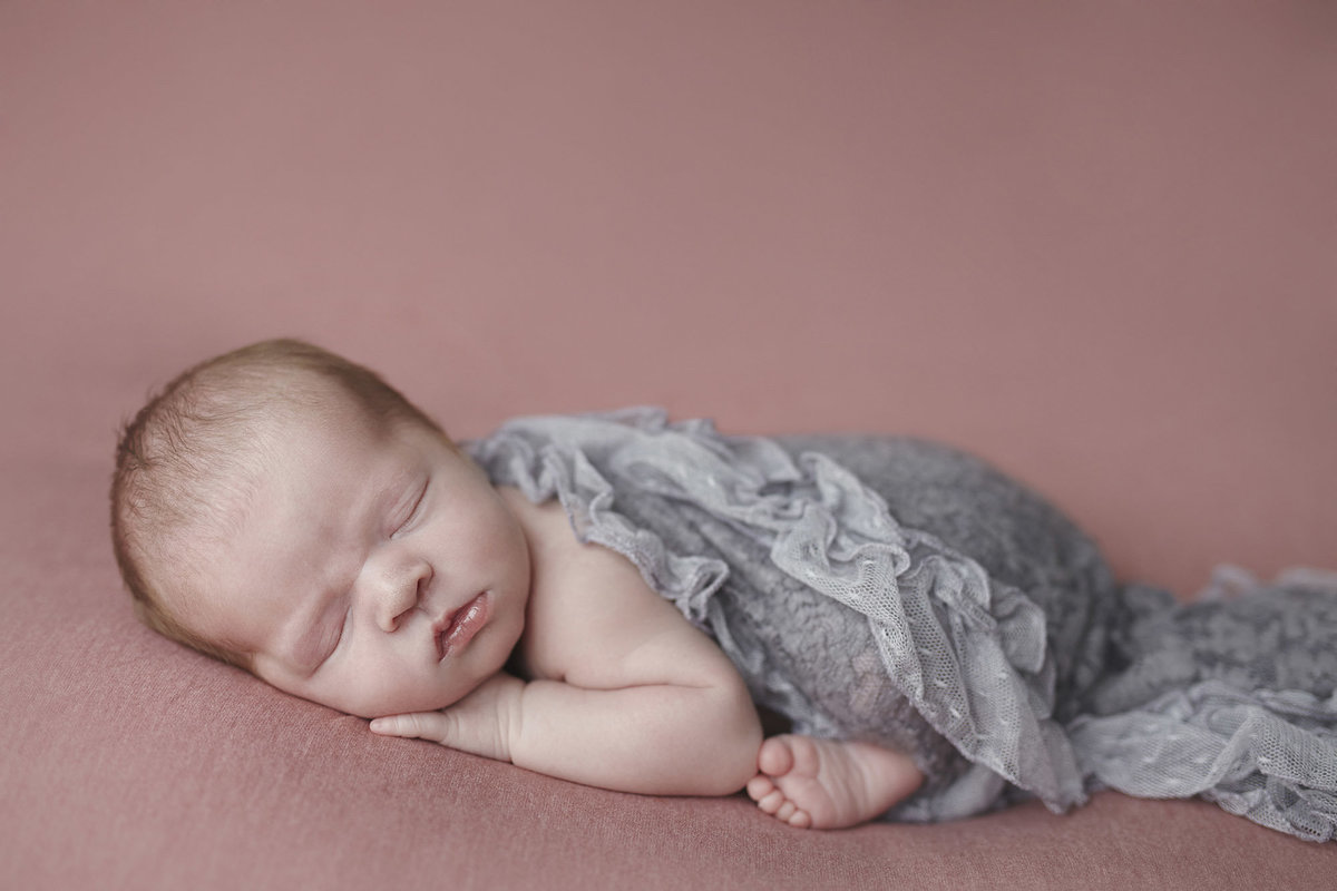 Newborn sleeping baby on a pink blanket with a grey blanket over her body