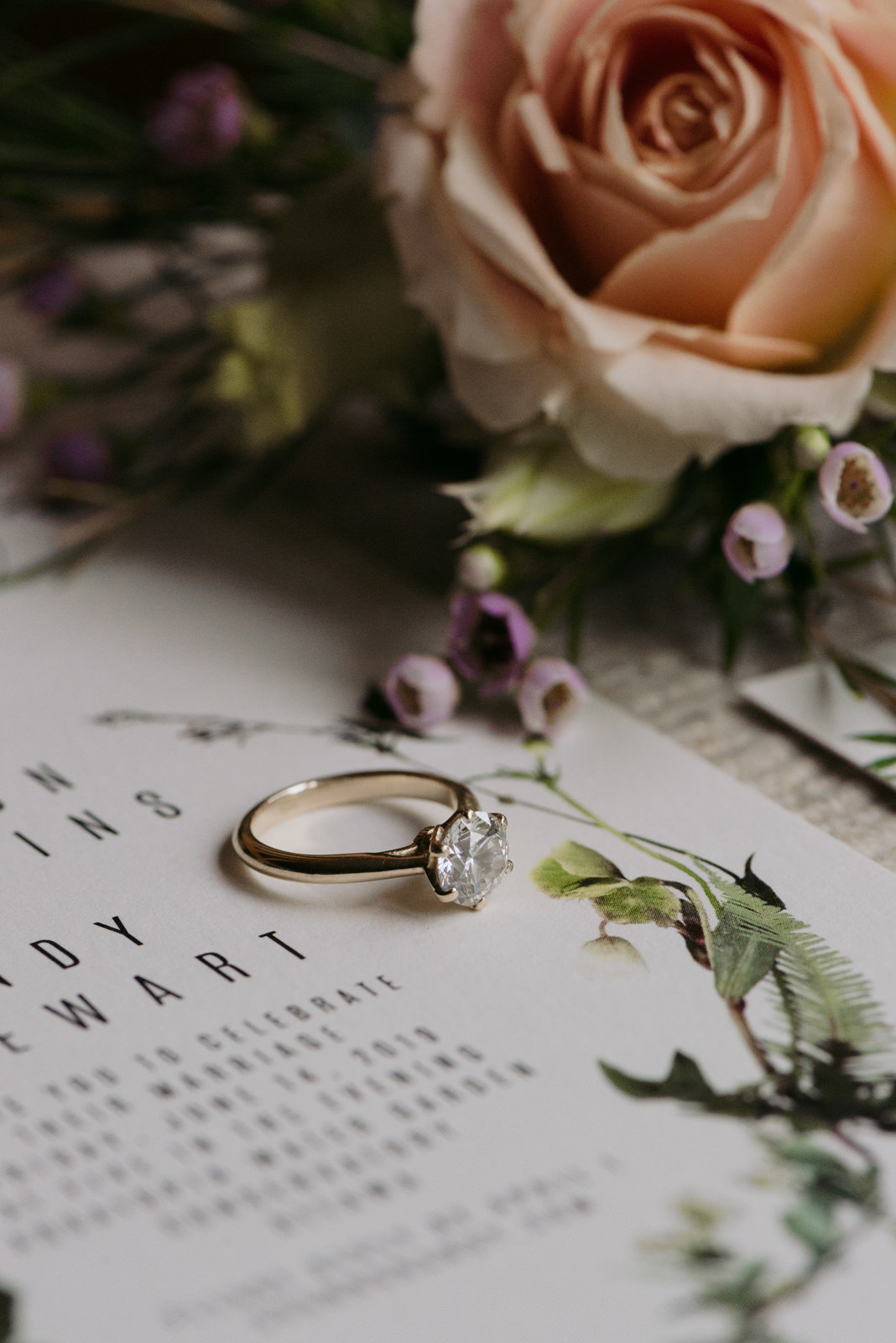 diamond engagement ring on wedding invitation with flowers