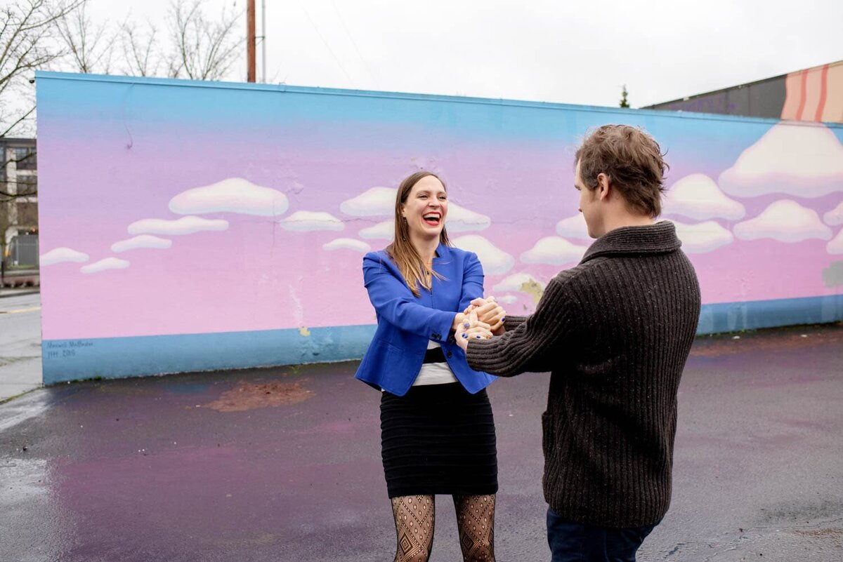 a couple spin and laugh in front of a pink and blue cloud  mural in kenton