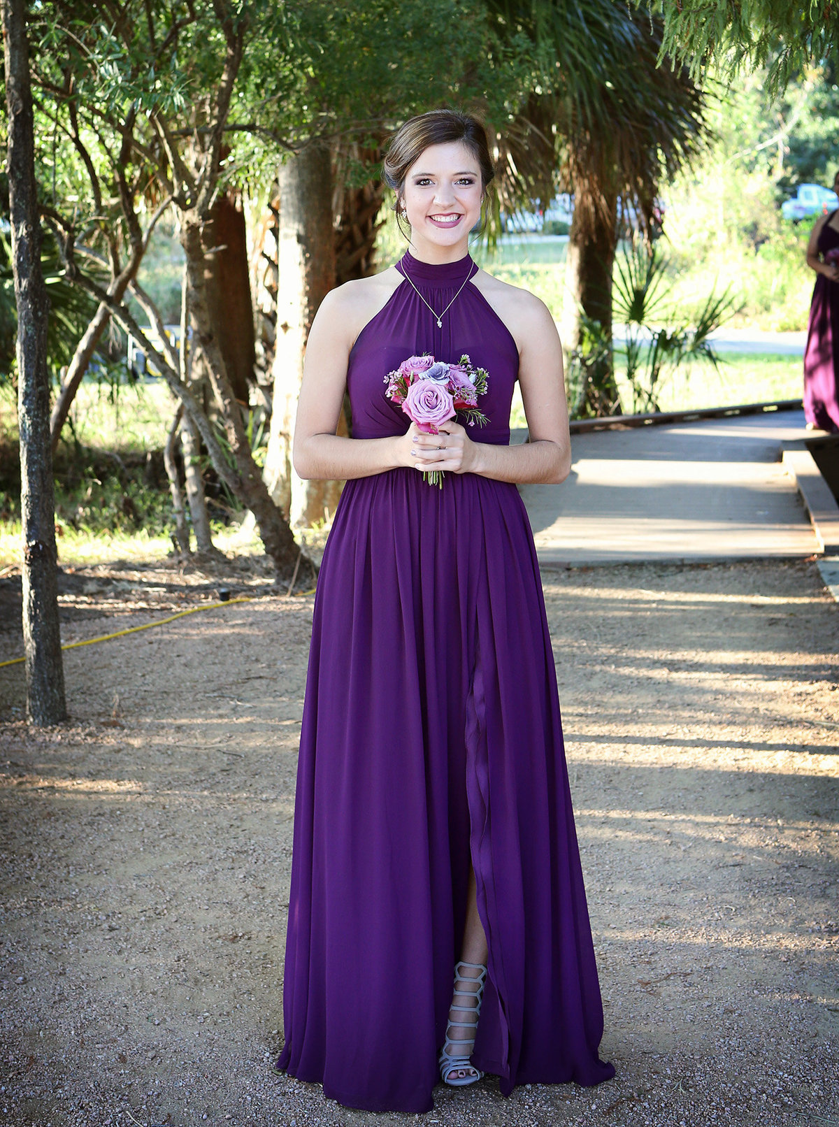 bridesmaid in a purple dress stops to pose before walking down the aisle in a wedding at City Park, New Orleans