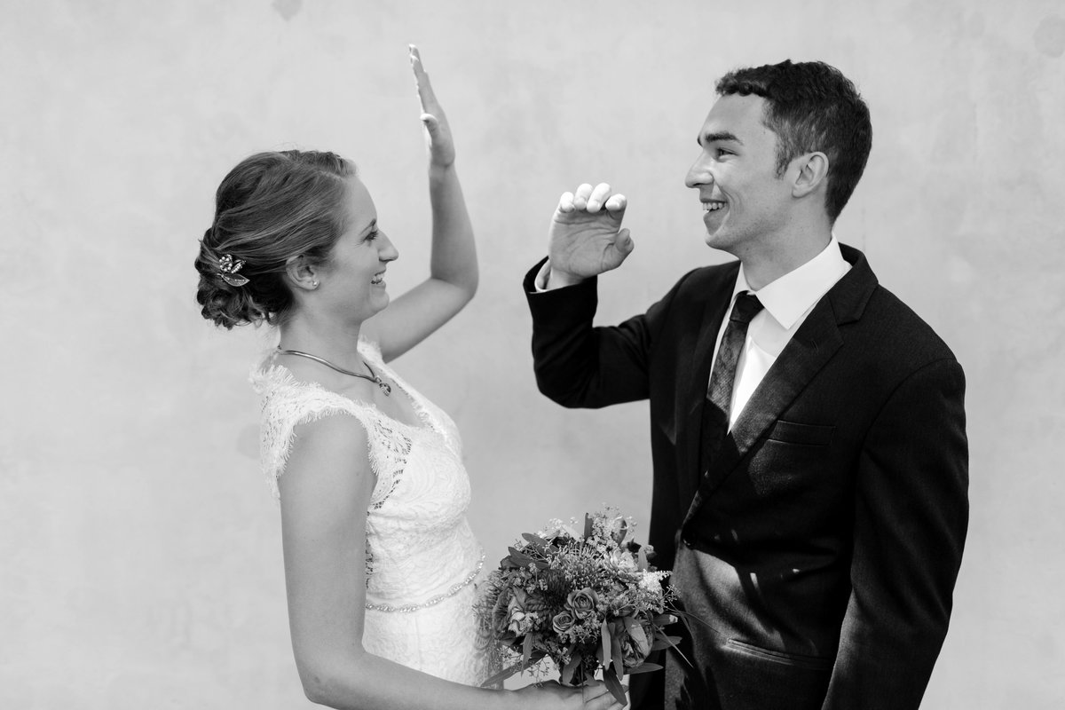 a couple high fiving on wedding day