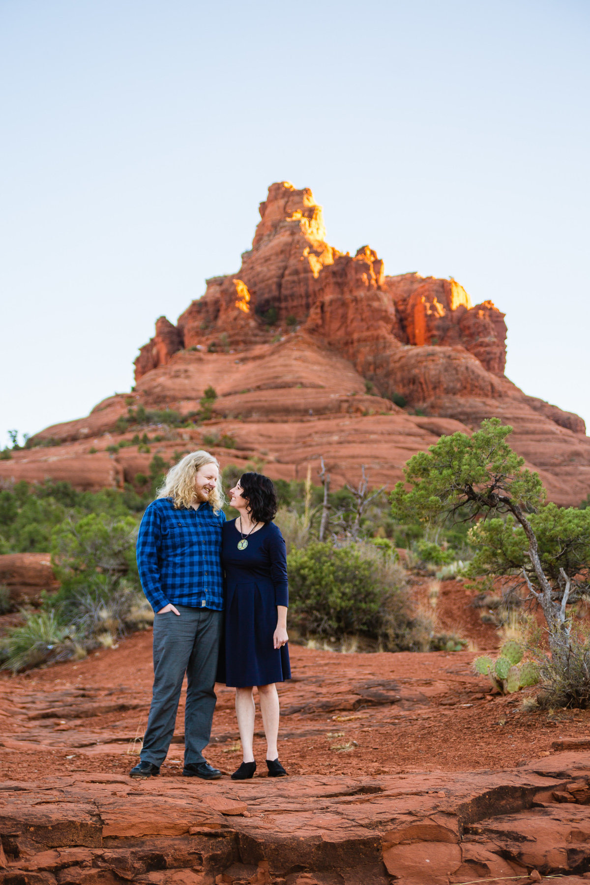 Couple looking at each other in front of Bell Rock during their adventure engagement session by PMA Photography.