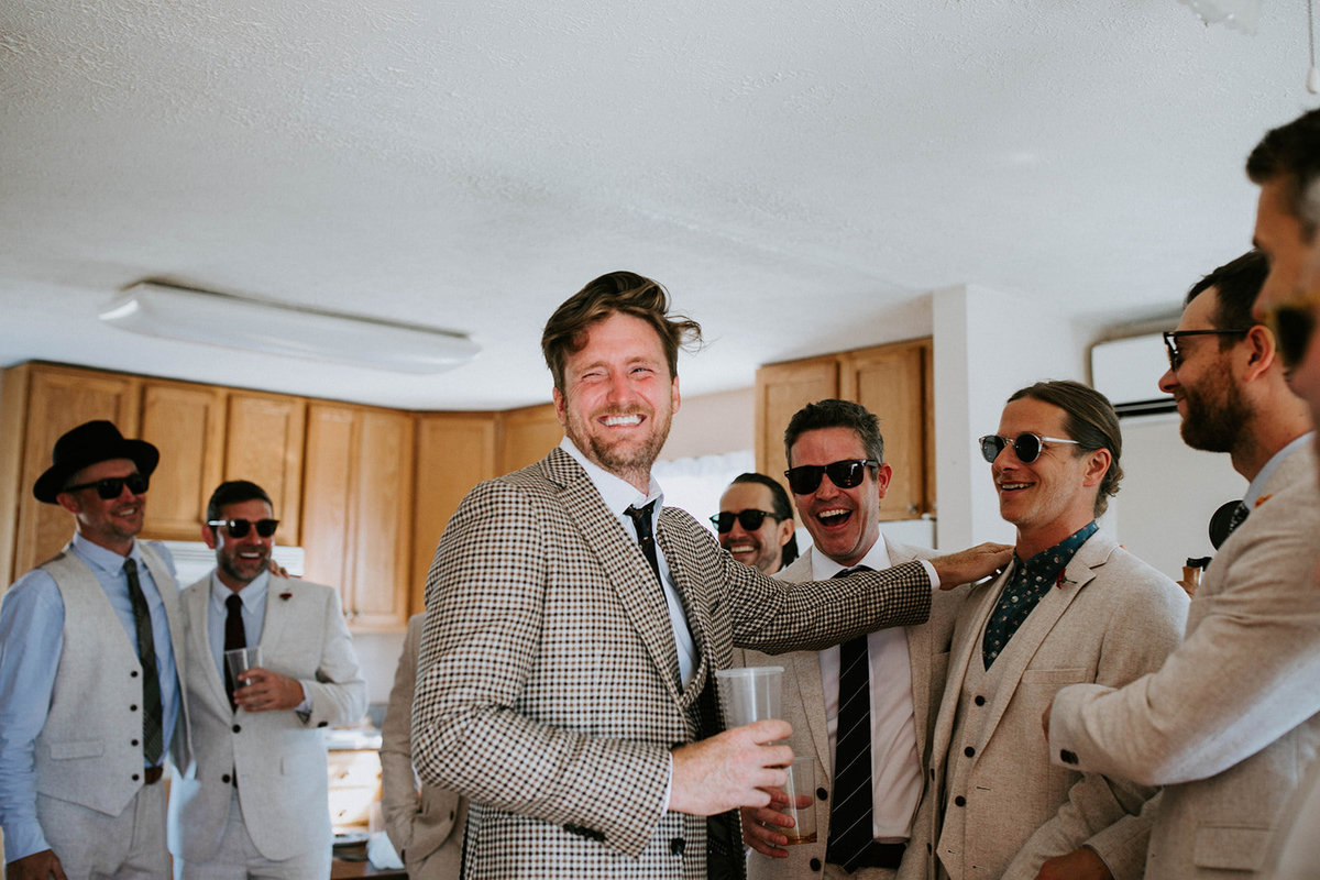 A groom laughs with his groomsmen.