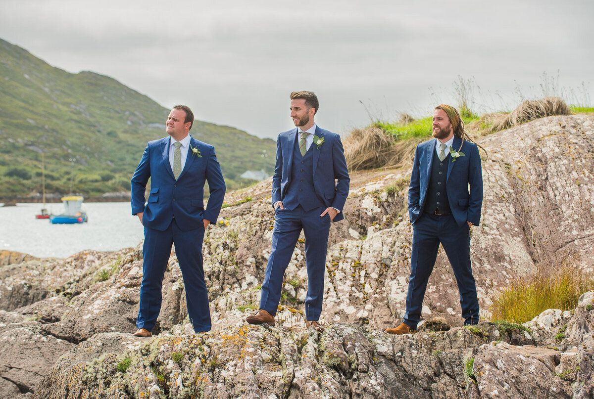 groom and his groomsmen wearing a blue suit and green, tweed tie standing on rocks overlooking Castlecove, Kerry