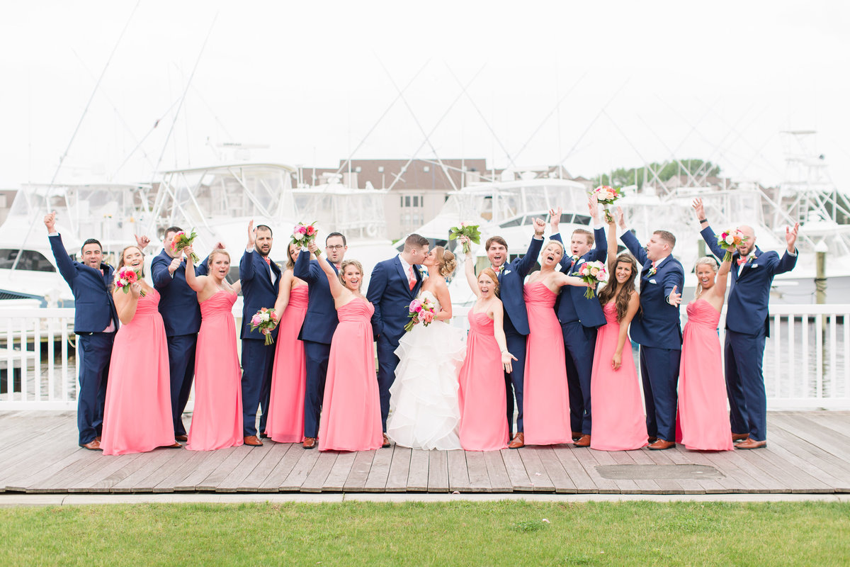 Wedding party cheering while bride and groom kiss at The Water Table
