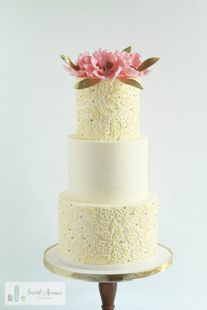 white wedding cake with piped lace and flower topper