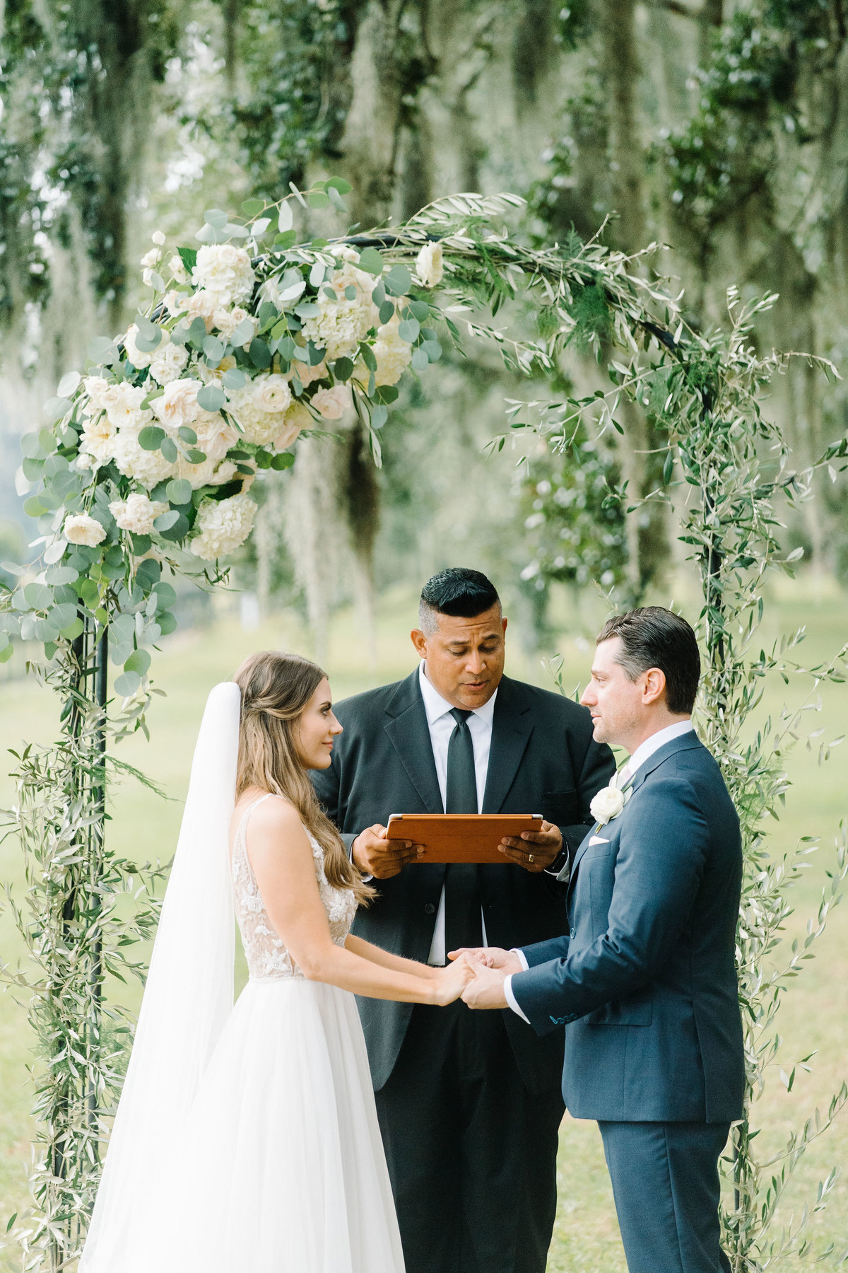 Bride and Groom under Greenery and Asymmetrical Ivory White Floral  Arbor