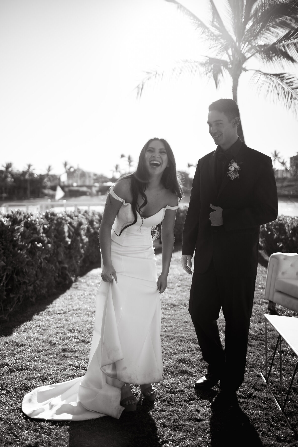 Bride laughing at the camera while she and the groom are walking on the lawn