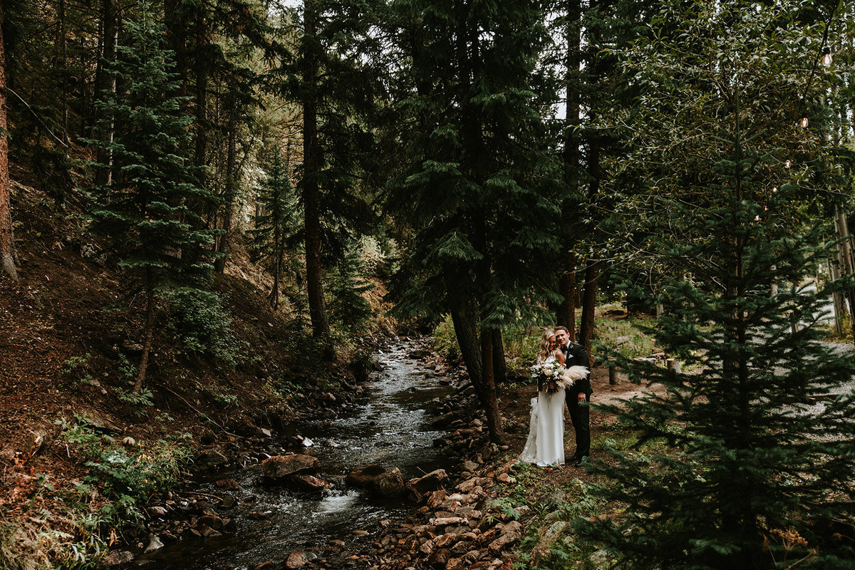 couple cuddling by the creek running through the Blackstone Rivers Ranch property in Idaho Springs, CO