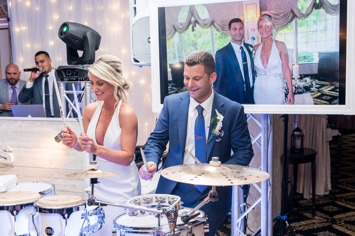 Bride and groom playing the drums at Giorgio's Baiting Hollow