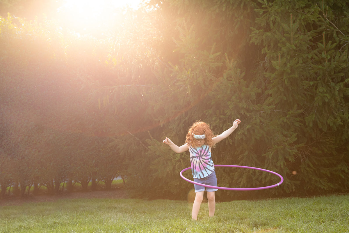 Little girl plays with hula hoop with arms in the air and beautiful sunlight behind her