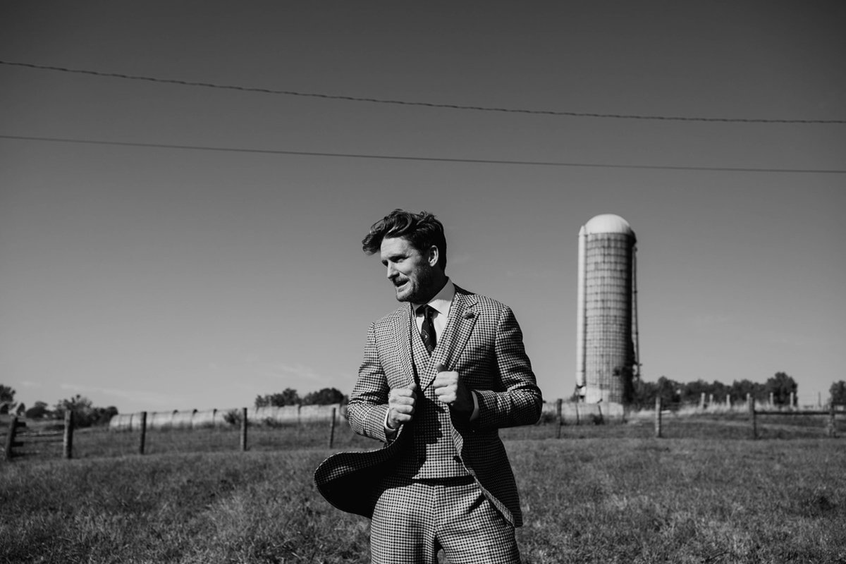 A groom stands with a silo in the background.