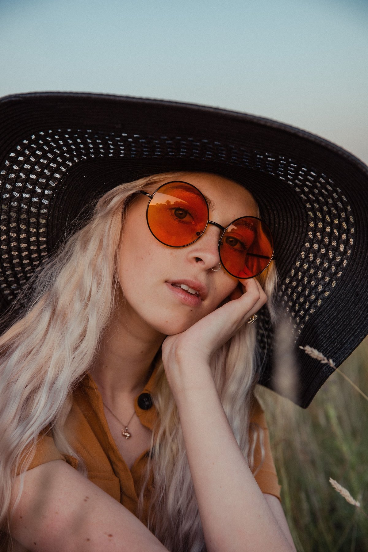 Amber sitting in the grass at golden hour, wearing orange sunglasses and a black straw hat