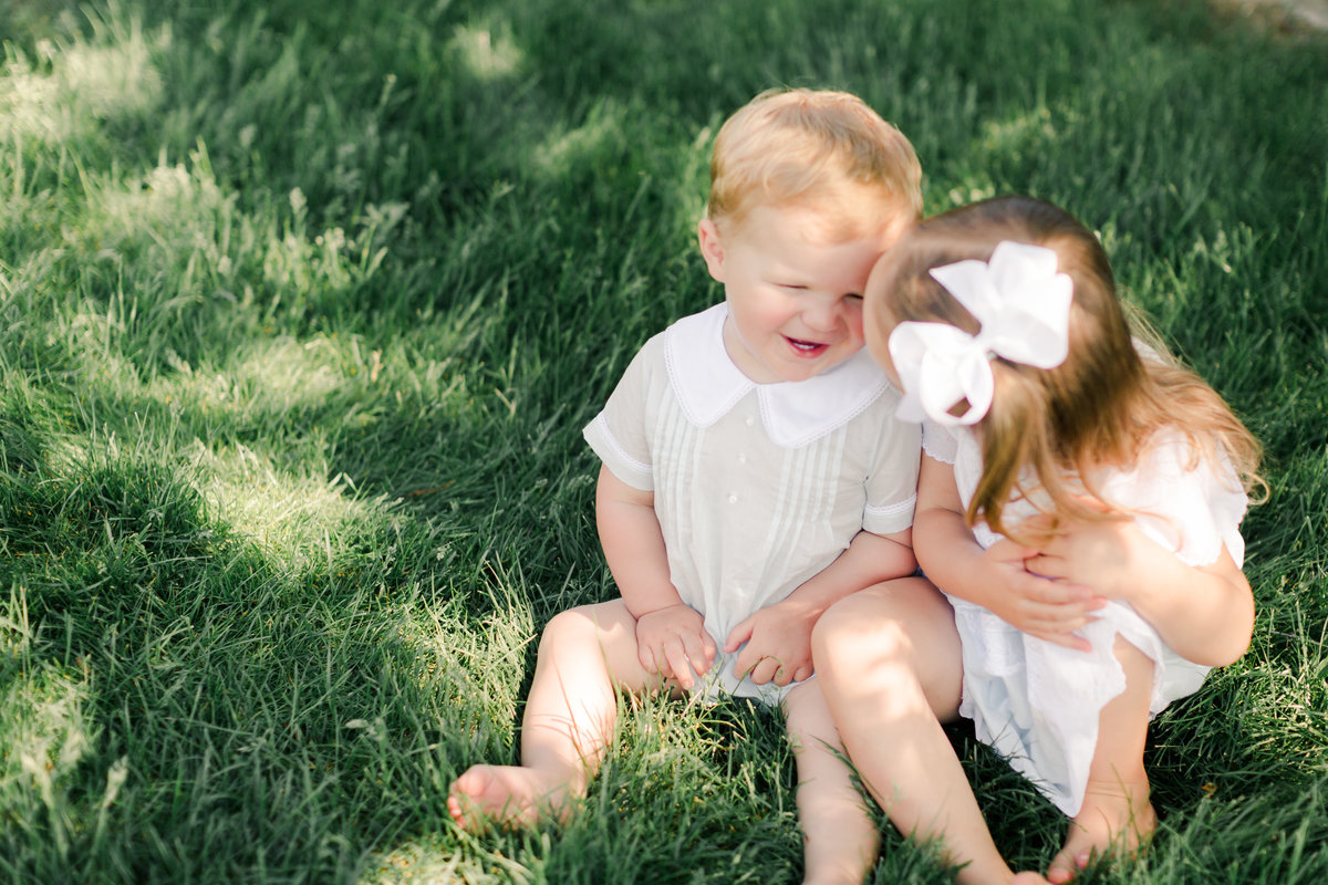 siblings laugh with each other on summer grasses in sunlight