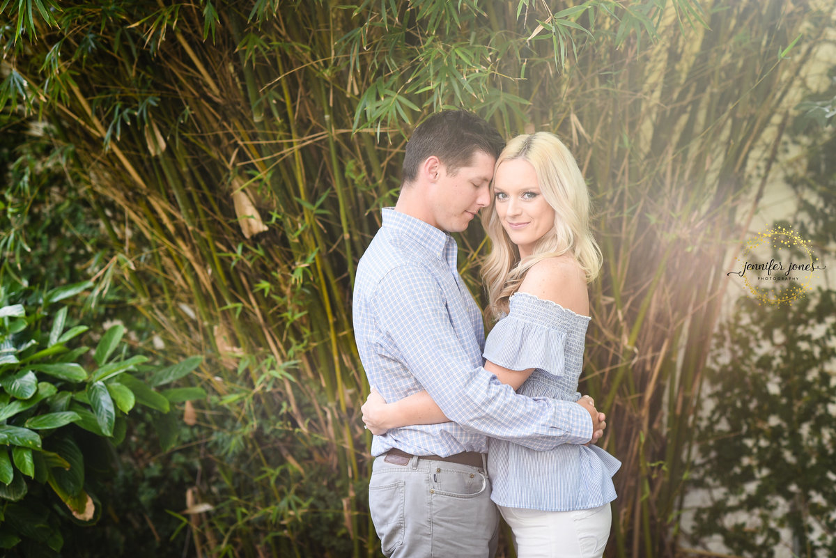 Beautiful Mississippi Engagement Photography: couple embraces in front of sunlit bamboo at Mary Mahoney's in Biloxi MS