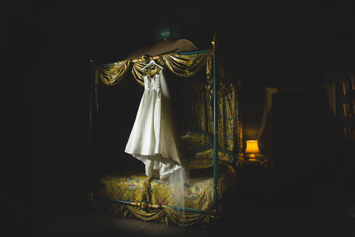 a wedding dress hanging on the four poster bed at sezincote house