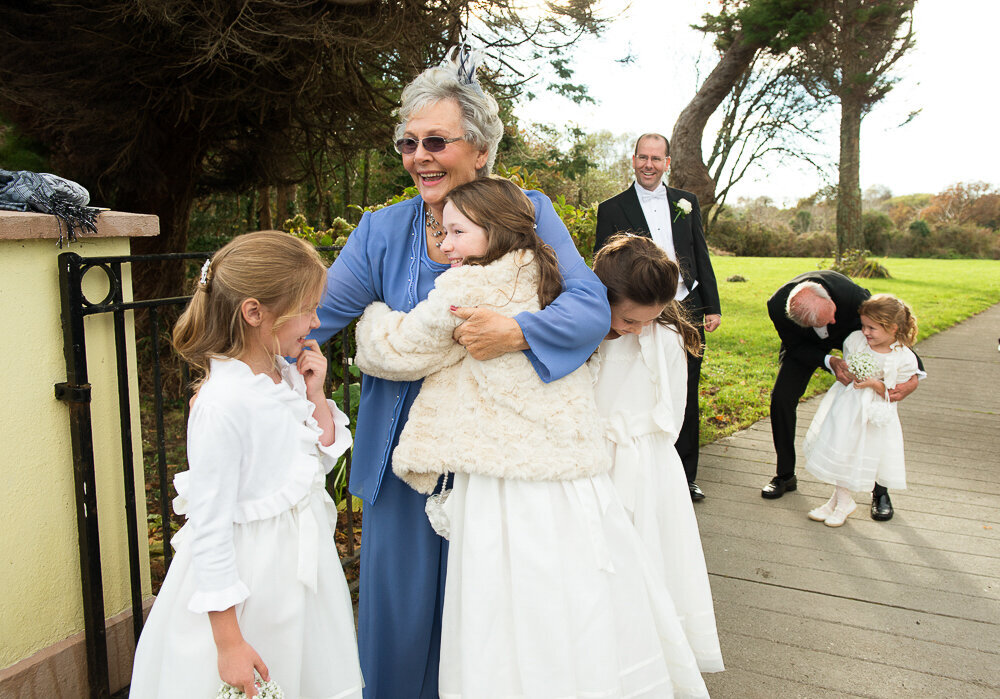 Grandmother wearing blue hugging her flower girl grandchildren at the gate of a church in Kenmare