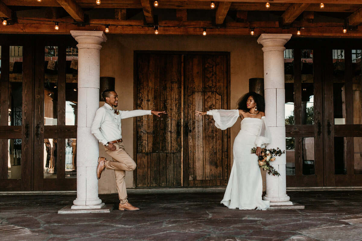 bride and groom  standing against a pillar