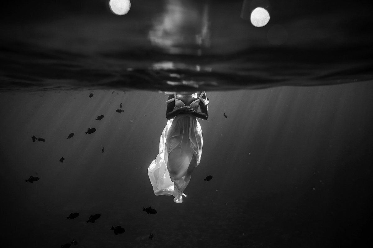 Maui bride trashing the dress underwater in black and white with fishes swimming in the backgroun