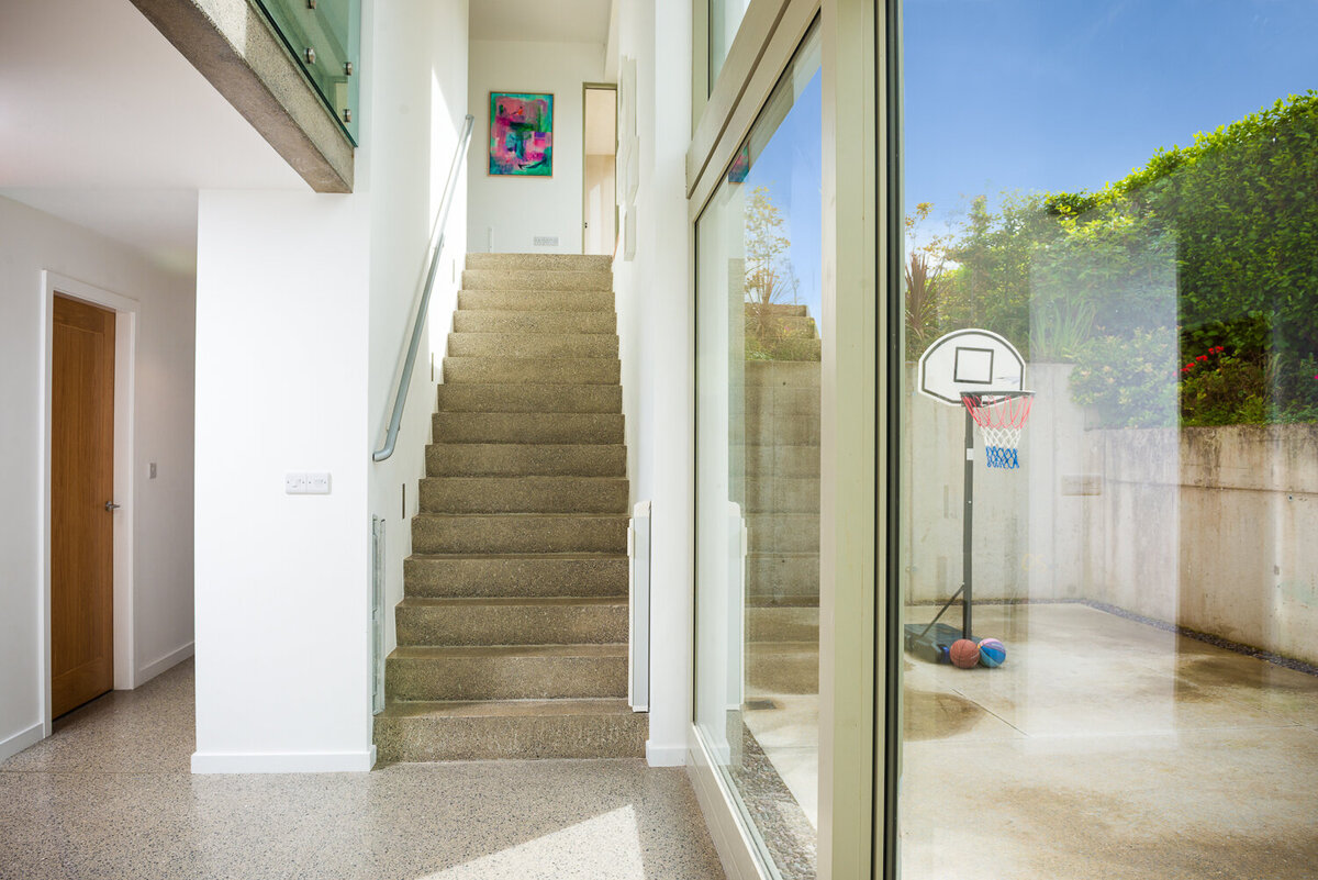 Architect designed house below level with concrete floor and stairs with ceiling height glass