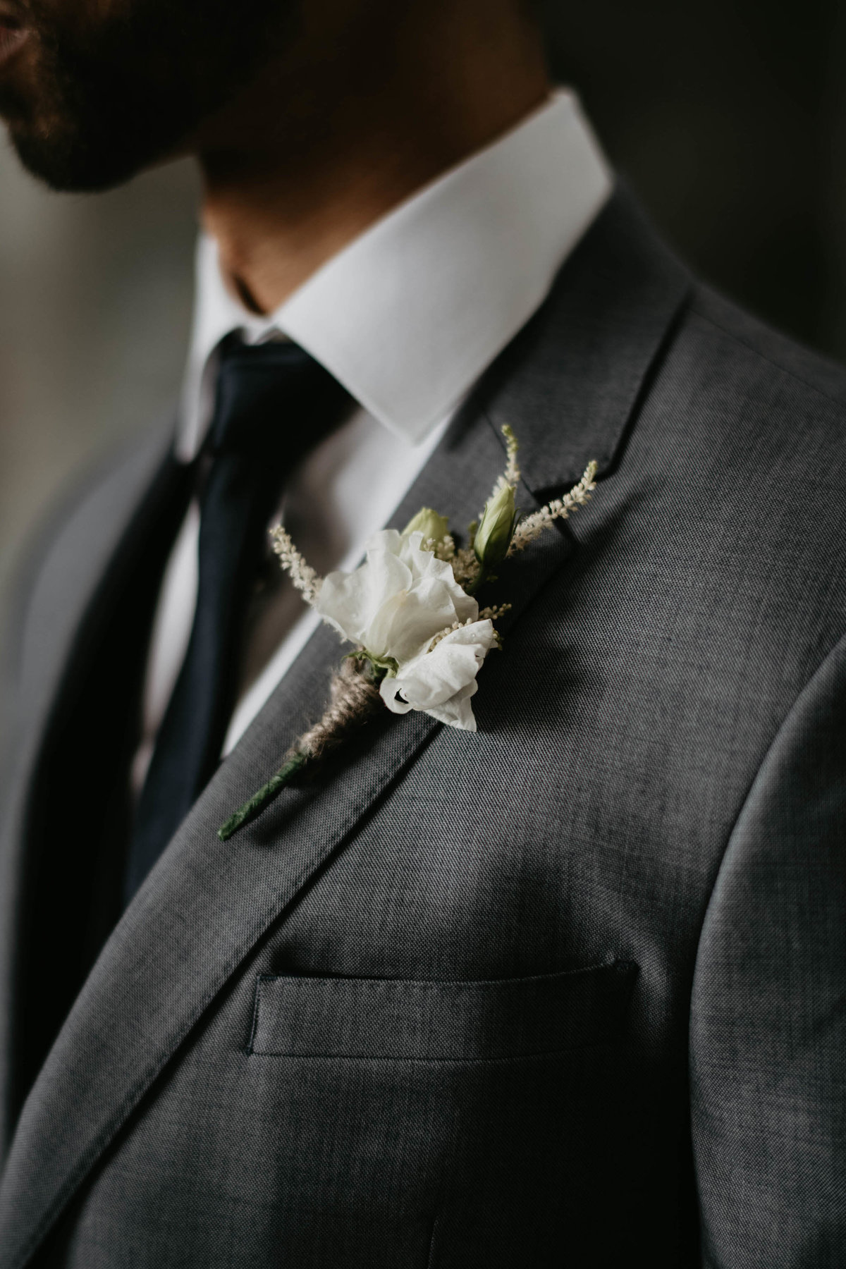 rustic wedding boutonniere pinned on grooms lapel