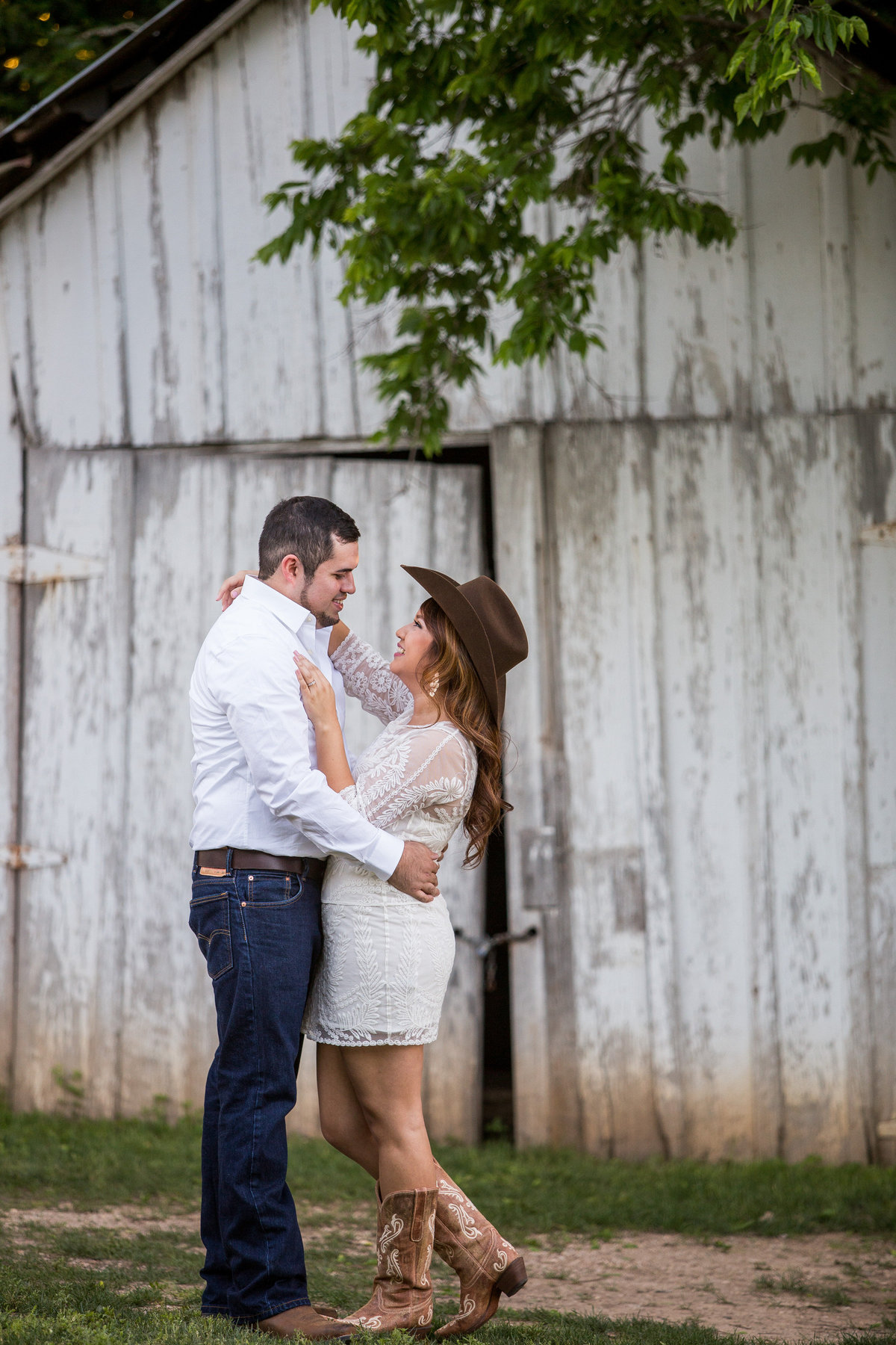 Engagement session a Gruene where woman wears her fiancé's cowboy hat and lifts her leg.