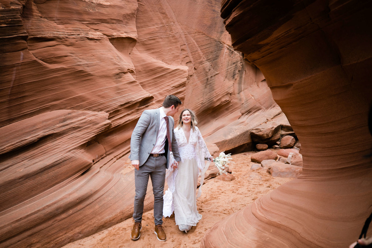 the groom looks back at his smiling bride as he leads her through the smooth slot canyon halls
