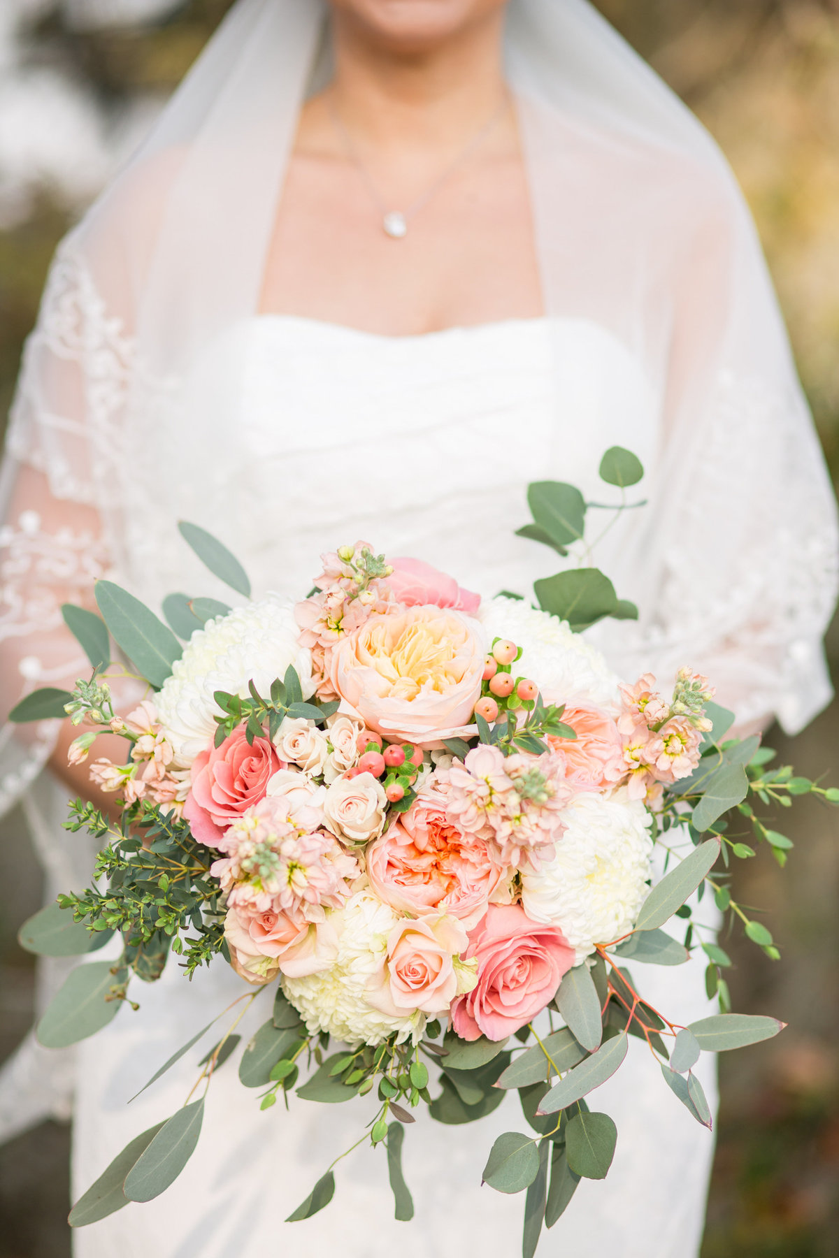 close up of bride holding a peach and pink bouquet of flowers