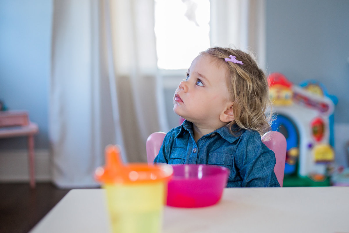 Little girl watching TV during lifestyle family session with Jennifer Blaak Photography