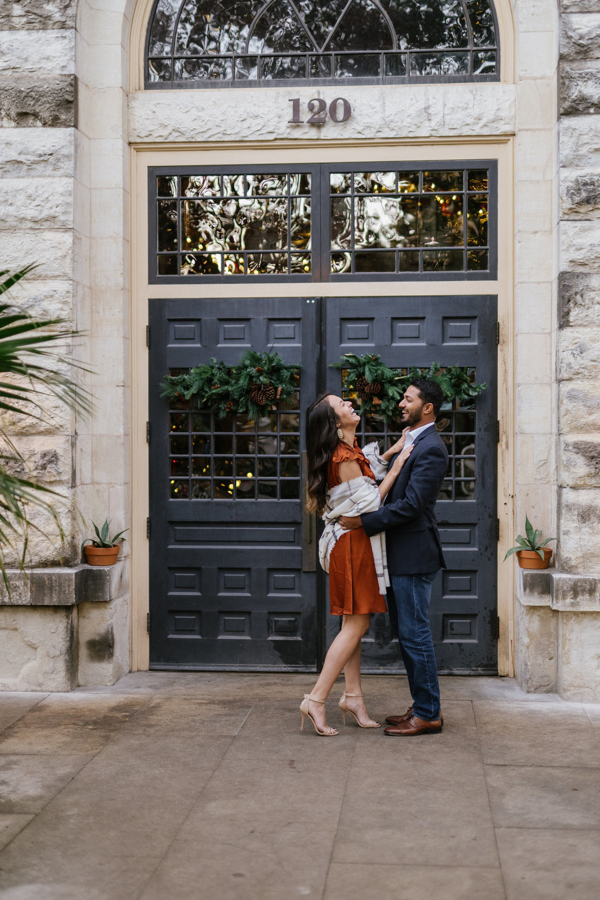 Engaged couple holding each other in front a door at the Hotel Emma at the Historic Pearl by the San Antonio River Walk.