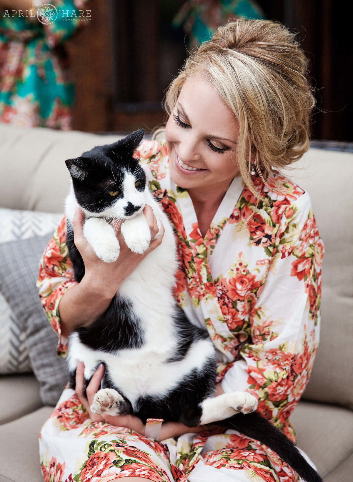 Bride in a floral robe snuggles her farm cat on her wedding day in Boulder Colorado