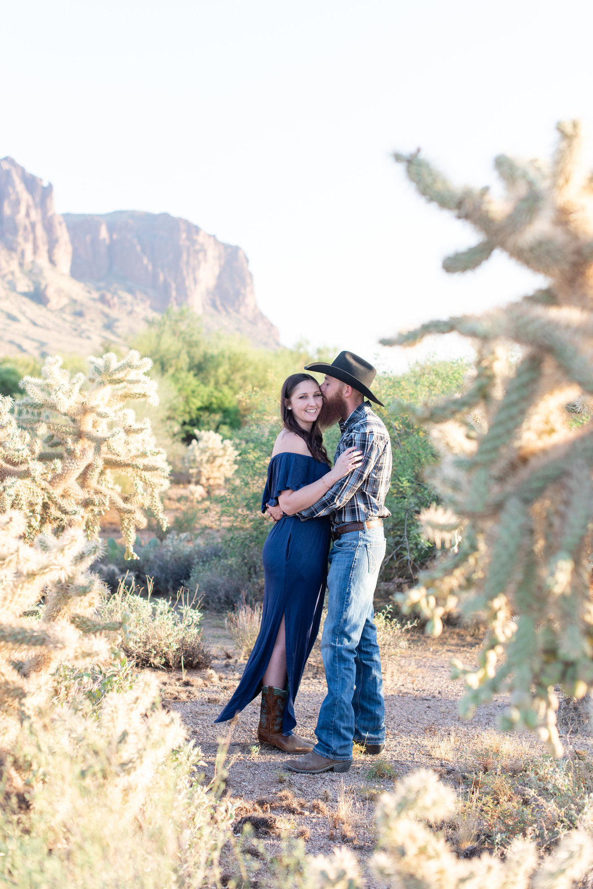 boy kisses girls cheek in the middle of cactus at lost dutchman