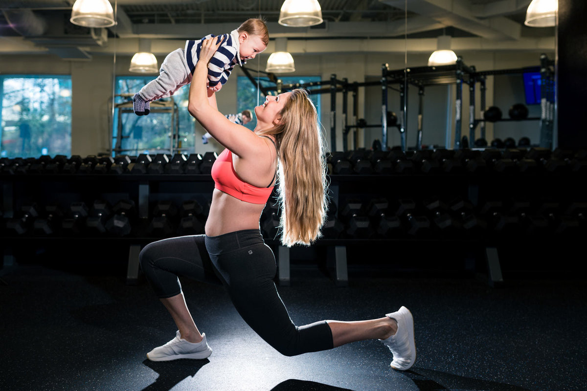 exercising mom lifts baby son in Atlanta gym