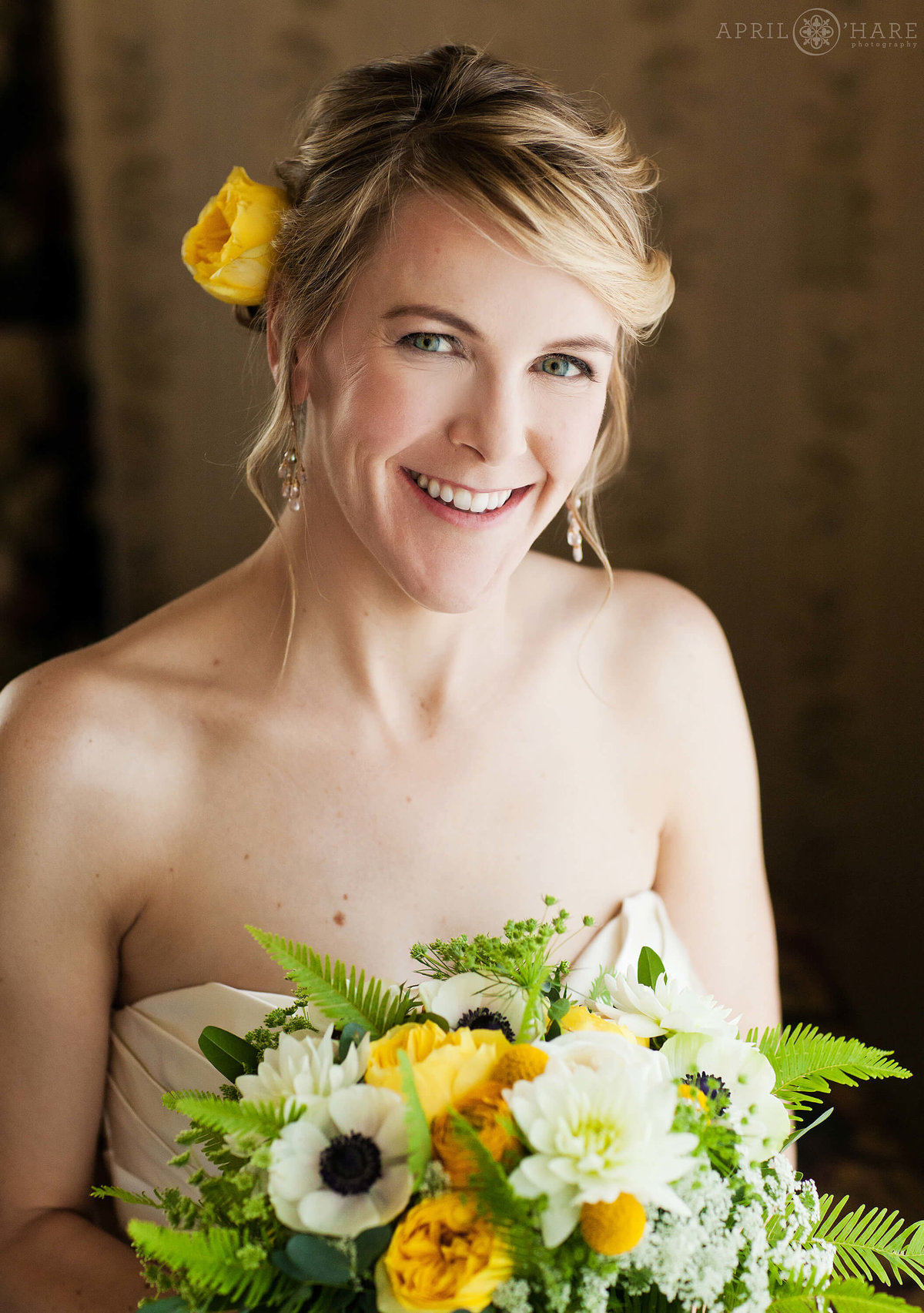 Natural light bridal portrait of bride with yellow rose in her hair at Hotel Boulderado