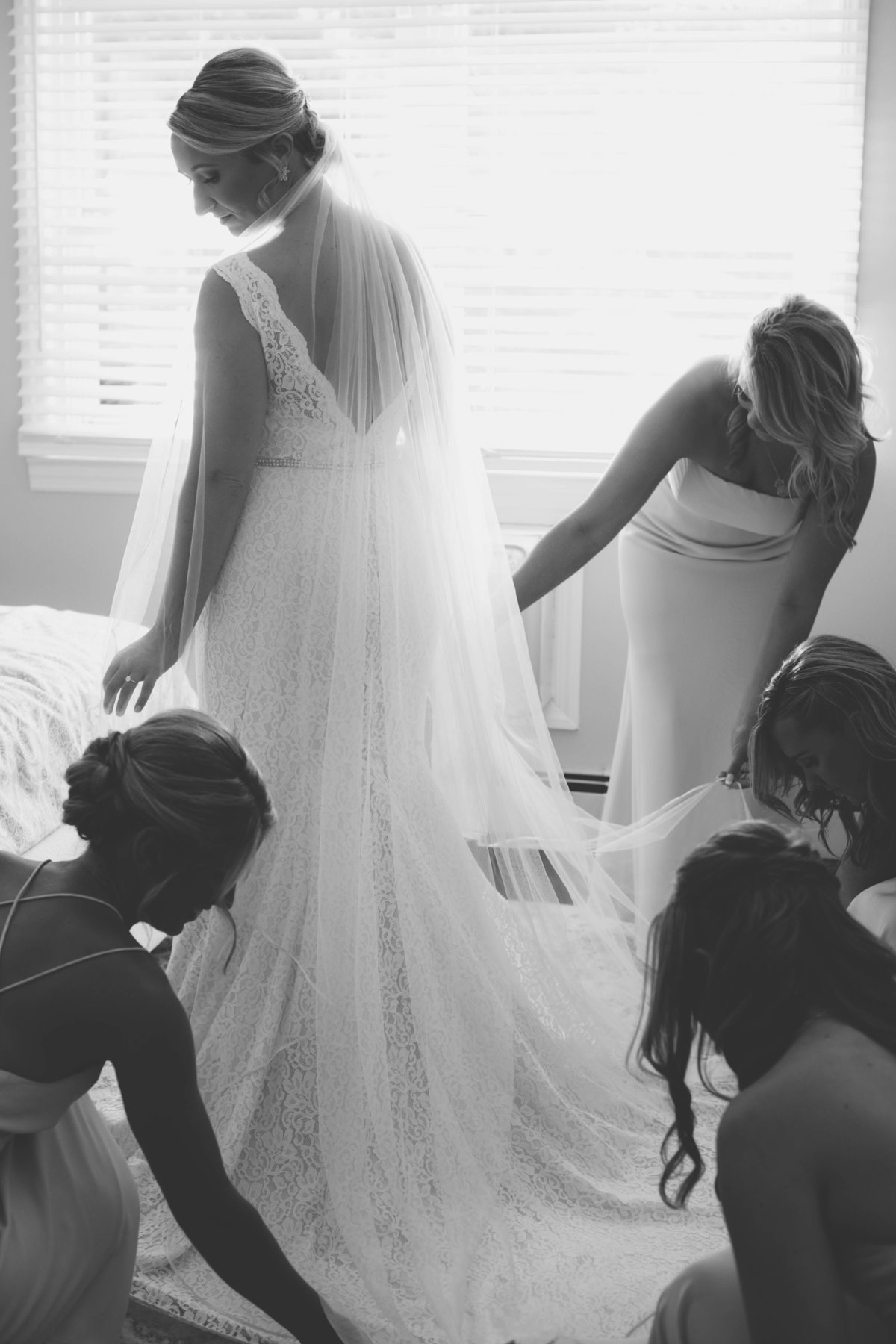 bridesmaid helping bride with dress in black and white photo from wedding at The Mansion at Timber Point