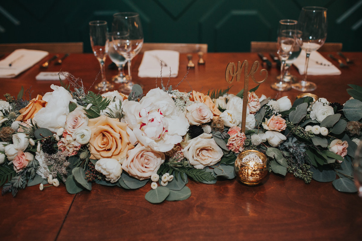 Wedding reception table with large eucalyptus garland with white flowers at The Fig House