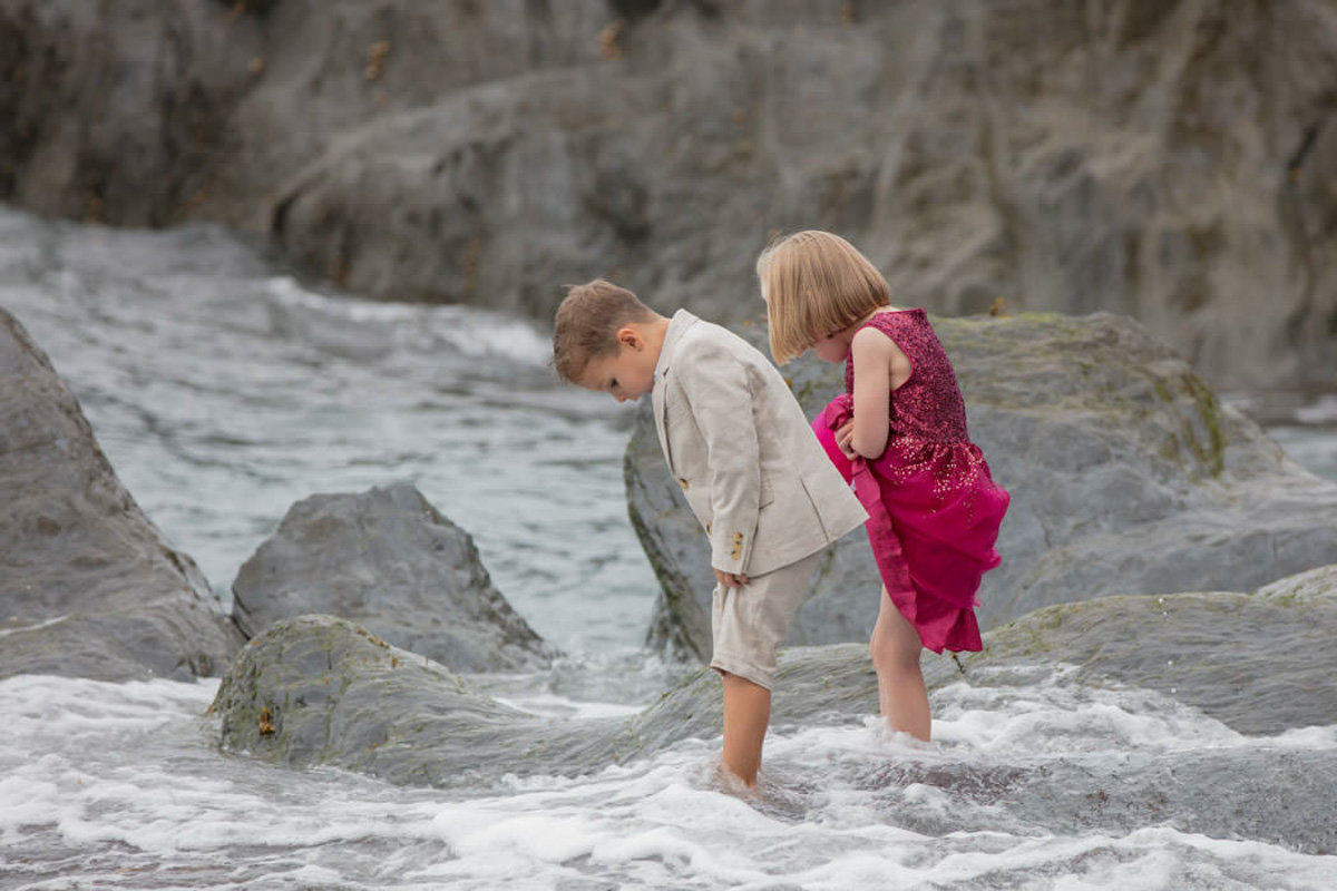 Flower girl and page boy barefoot in the sea at Tunnels Beaches Devon