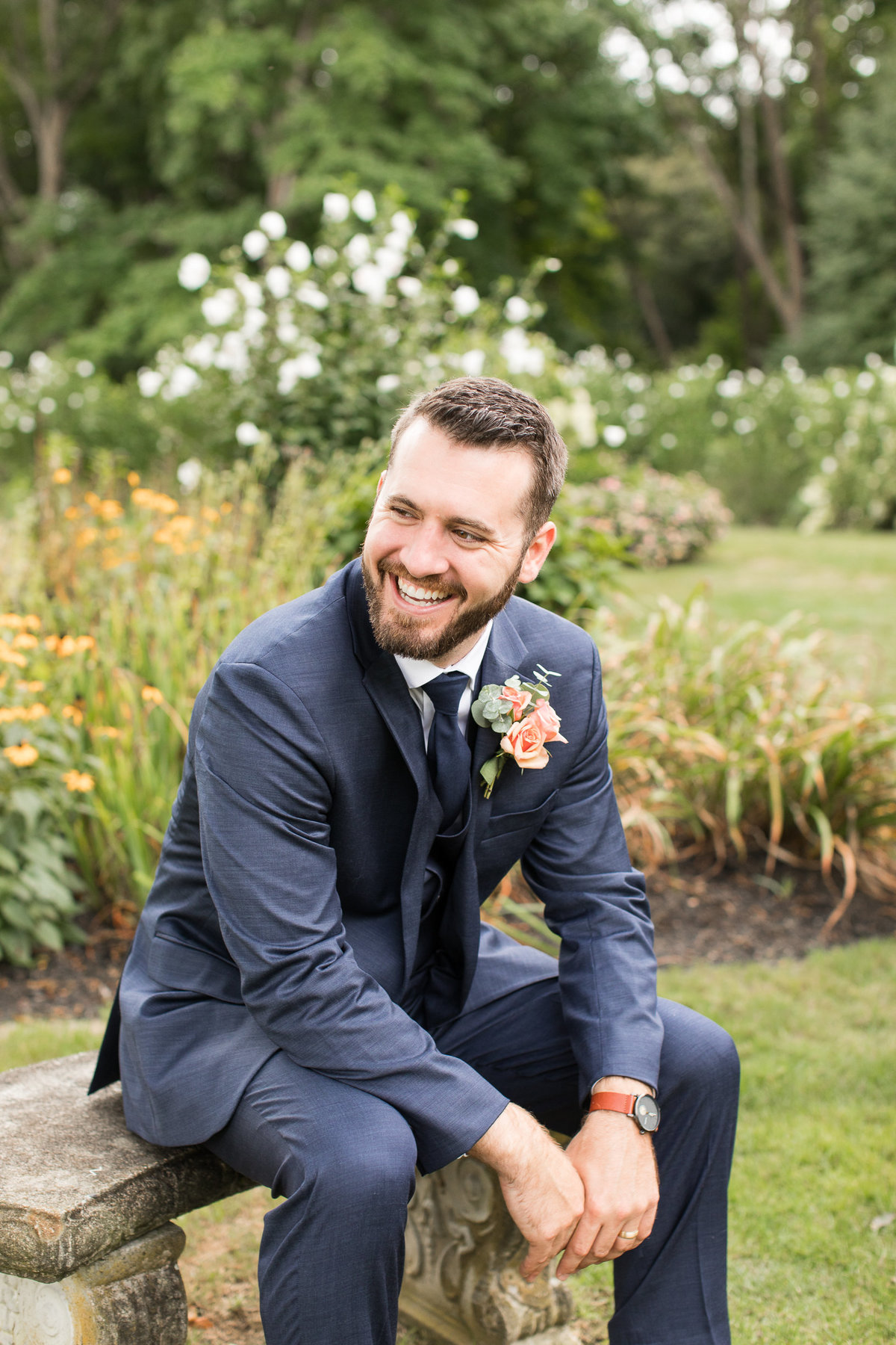 Groom poses on a garden bench at Glen Manor House