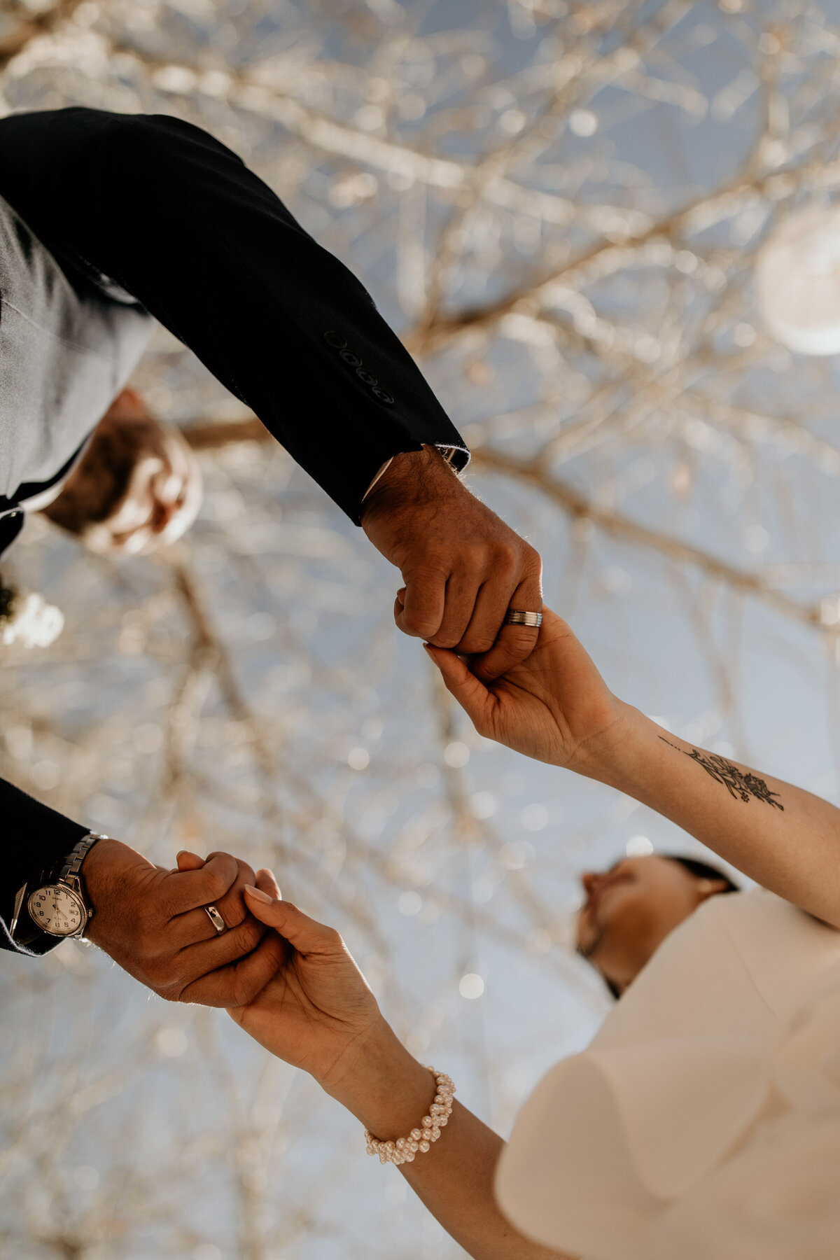 Bride and grooms hands holding from below