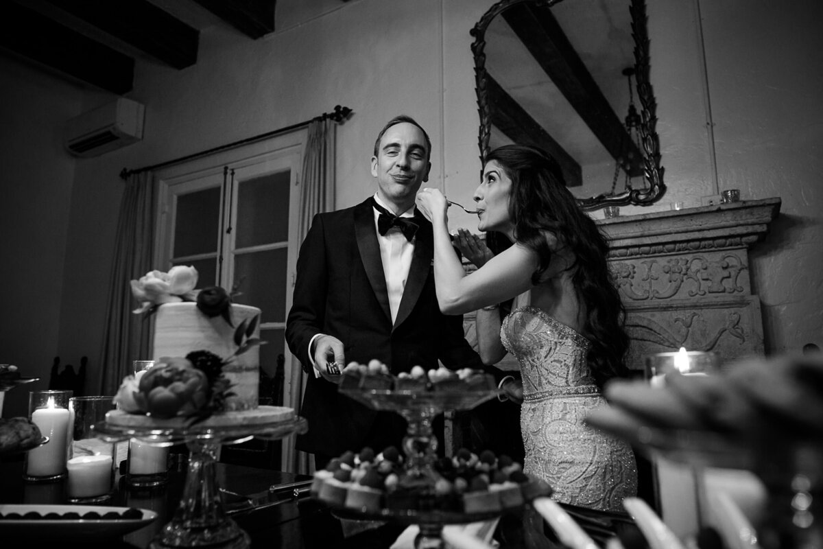 black and white image of a bride and groom taste their wedding cake at Villa Woodbine