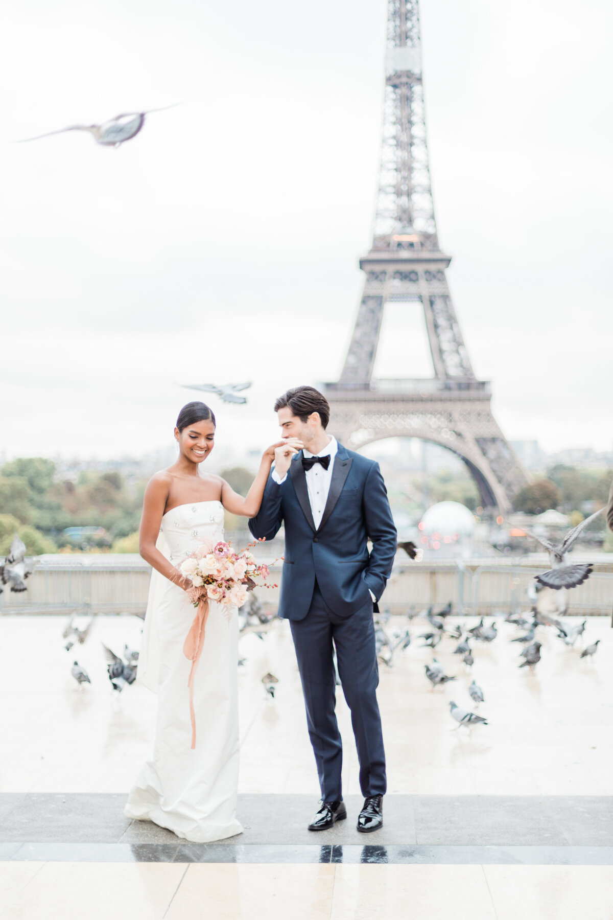 couple standing under Eiffel tower with birds flying by costola photography