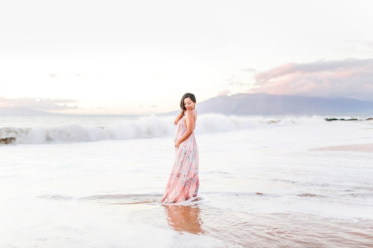 Pregnant woman poses on a Maui beach during her maternity portrait shoot
