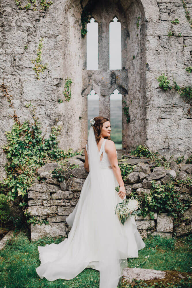 Ireland & US Wedding Coordinator, bride posing under rock archway