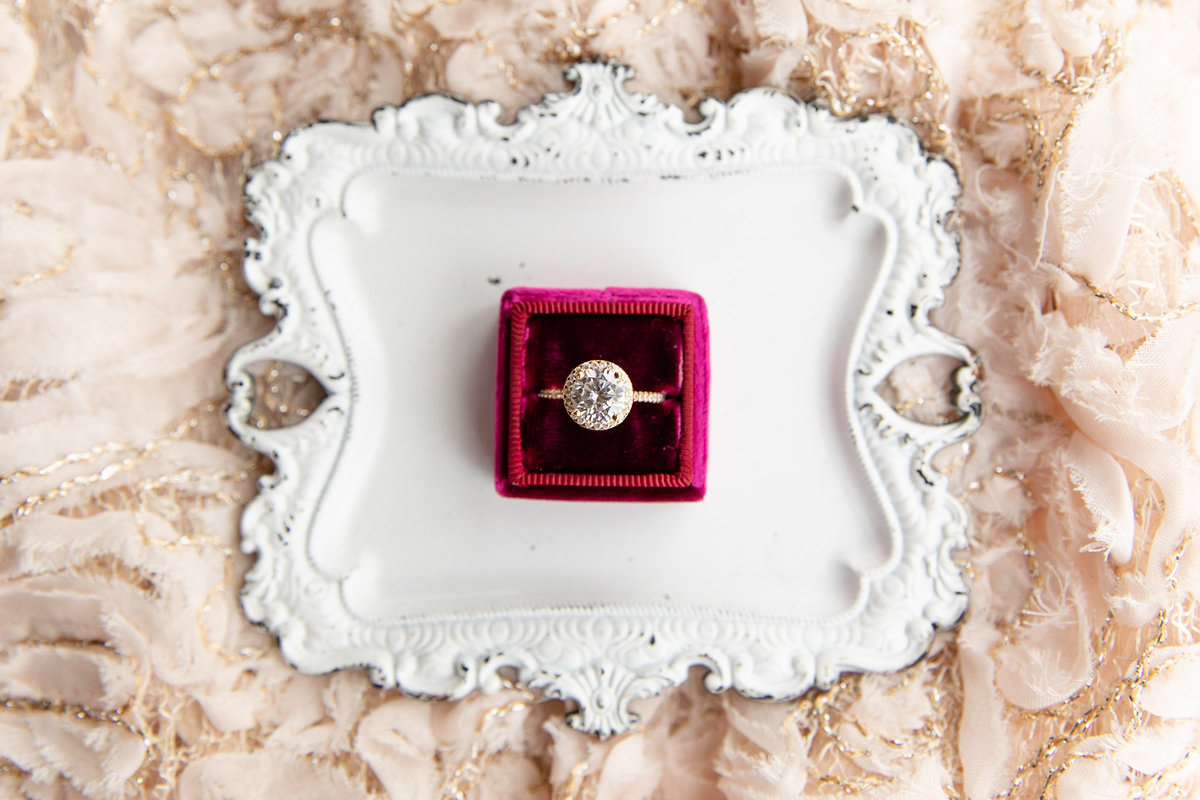 engagement ring in Mrs box on top of a vintage white tray