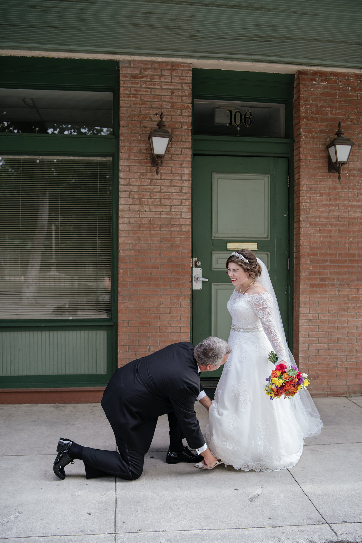 Father of bride putting a sixpence in brides shoe just before wedding ceremony at The Spire venue in downtown San Antonio